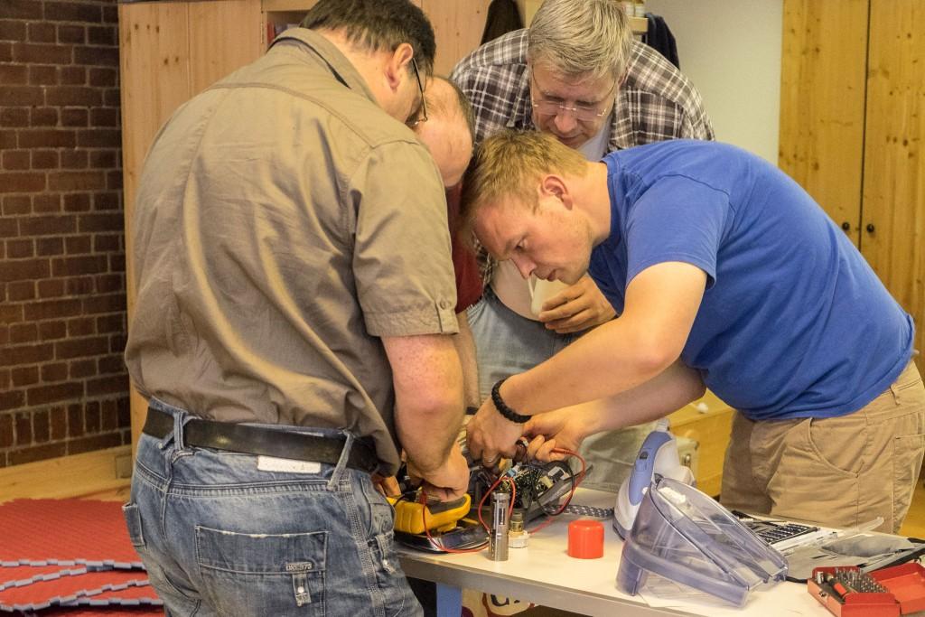 vier Techniker gegen den Dampfbügelautomat